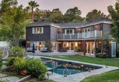 Neil Patrick Harris' home in Sherman Oaks, California has grey shingle siding, stacked balconies, white railings, white shutters, double doors, outdoor furniture, and a large pool with stone deck.