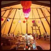 The decorated tipi, worth the hours of effort! Wedding tipi paper pom poms venue