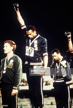 Olympic Games, Mexico City, Mexico, Men's 200 Metres Final, USA gold medallist Tommie Smith (C) and bronze medallist John Carlos give the black power salutes as an anti-racial protest as they stand on the podium with Australian silver medallist Peter Norman