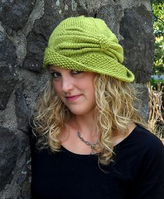 A stylish head topper for winter, Cloche Divine harkens back to a time when hats were not only high fashion but absolutely fabulous to wear as well. Worked in a fantastic green superwash worsted merino wool, this cloche features a wide border of seed stitch for the brim. The stunning bow is created by making short rows and then gathering them together by purling together two rows at once. A small seed stitch tab is picked up and knit from the stitches on the hat before the gathers and then…
