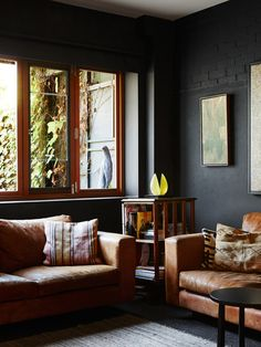 Living room. Sofas by Arthur G. Artwork above small revolving bookcase by Rick Amor, and lemon sculpture from Italy. 'The wall of green Boston Ivy creates beautiful shadows and light,' says Amanda. Photo – Annette O'Brien. Production – Lucy Feagins / The Design Files.