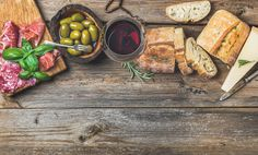 #Wine snack set and glass of red wine  Wine snack set. Glass of red wine green mediterranean olives prosciutto salami and aged cheese over rustic wooden background. Top view copy space horizontal composition