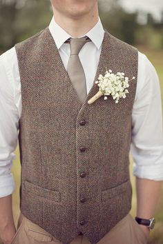 Groom in warm brown tweed vest in herringbone pattern with baby's breath boutonniere.