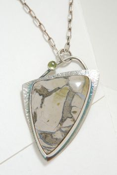 Unique would definitely be an appropriate description for this pendant! This stone alone has its own special qualities... The colors are subtle,