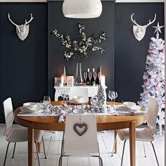 un sapin de Noël blanc et boules de Noël argentées sur la table