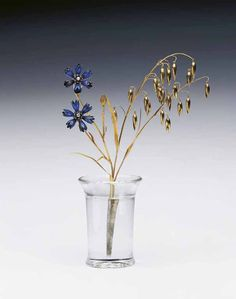 This study of cornflowers and oats is one of Fabergé's most exquisite creations. It was purchased by Queen Elizabeth and Queen Mary, respectively the mother and grandmother of the present Queen Elizabeth II (then Princess Elizabeth), on 27th June 1944. Queen Elizabeth described it as 'a charming thing and so beautifully unwarlike'. The piece was purchased to cheer up Princess Elizabeth's 'shelter room' at Buckingham Palace – hence the reference to 'unwarlike'.