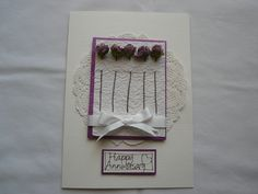 Stick paper doily to 5x7 card. Long stemmed paper roses pushed through hand made paper & mounted on coloured matt. Ribbon tied round topper before placing on top of doily. Add a matted & layered greeting.