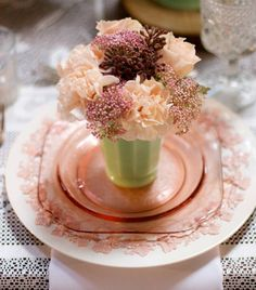 A pretty table setting using pink depression glassware and vintage looking flowers.