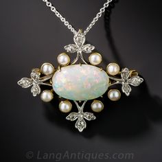 This original Edwardian era delicacy - circa 1910 - is designed around an enchanting, horizontally set oval opal, weighing 2.75 carats (measuring 7/16 inch across), glowing with a rainbow palette of bright pastel colors. The gemstone is framed by eight lustrous half pearls and four diamond-set trefoil foliate motifs. Beautifully hand fabricated in platinum over 18K yellow gold, this thoroughly lovely pin/pendant necklace combo measures 1 1/4 wide by just over 1 inch high. The p...