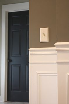 I love the white paneling and taupe walls, especially with the black door. It makes it feel grounded