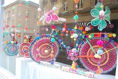 'Rio Carnival in Wool'. Yarn bomb bikes by Emma Leith in display in shop window in Bath