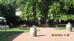 Cour intérieur : suspensions de boules chinoises, roses et blanches aux arbres. Petits vases fleuris sur tonneaux.
