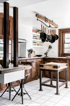At the center of the kitchen is an island work surface made of a Victorian-era butcher's block on a metal base. A pot rack and countertop lighting are both made of antique parts.