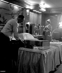 1948, A steward unpacks a passengers clothes in one of the state rooms, while a stewardess fixes a vase of flowers which have been sent aboard the Queen Mary liner (Photo by Popperfoto/Getty Images)