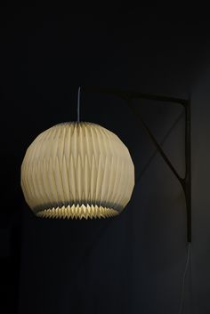 Sculptural wall lamp in teak with Le Klint shade at Studio Schalling