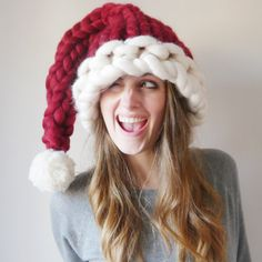 Chunky knit Santa Hat! Hand knit with a white rim, ruby red triangular shaping and finished with a big fluffy hand cut pom-pom. Perfect for the work Christmas party, Christmas Dinner or just as a decoration around the house. 100% merino wool