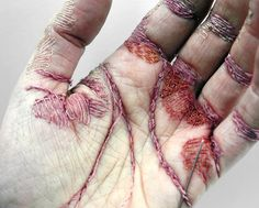 "The artist becomes the artwork in this new piece by Eliza Bennett called ""A Woman's Work Is Never Done."" Using the palm of her hand as her canvas, Bennett stitched the top layer of her skin with colorful thread aiming to create the image of an incredibly work-worn hand"