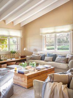 Salón con paredes en beige y techo con vigas en blanco con dos sofás y una butaca
