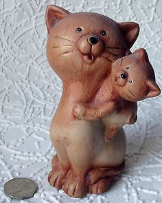 A pottery cat-and-kitten figurine It is about six inches tall Condition Fairly good condition There are a few small patches where the outer layer of