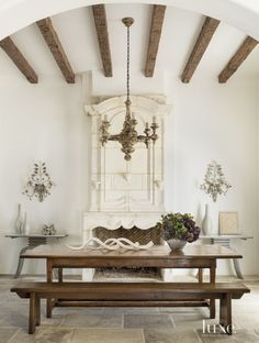 n the dining room, a rustic wood A table and benches, overseen by a carved antique Italian chandelier, offset the formality of the limestone floor and fireplace.