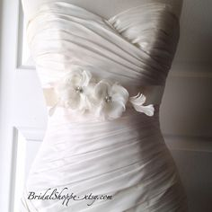Ivory Handmade Fabric Flower Bridal Sash Belt This listing is for one handmade USA fabric flower bridal belts. Flowers are mounted on a 3 yard long double faced satin ribbon belt. Accented ivory feathers on the side and pearl pearls /rhinestones centers. Message me about customizations. bridalshoppe Accessories Belts