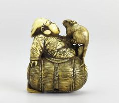Netsuke of carved ivory, Daikoku sitting on a bale of rice with a rat and a mallet, signed: Japan, by Rantei