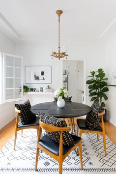 Mudcloth pillows at the dining table plus a gorgeous patterned rug add some flair to this light bright dining room.