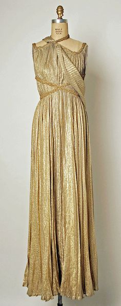 Evening gown designed by French designer, Marcelle Chaumont.  Grecian style champagne-colored gown of silk with metallic thread trimming around the neckline & as wrapping underneath the bosom.