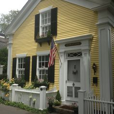 Yellow Cottage. Built 1853. Edgartown.  Yellow siding, black shutters, picket fence.