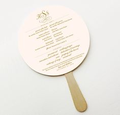 Ceremony program in paddle fan for outdoor wedding.