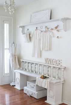 Not really crazy about the clothes hanging in the entry. Maybe hats or sprigs of flowers. All-white shabby chic entryway.