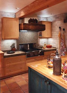A country kitchen that's both rustic and modern (somehow), with light brick walls, terra cotta floors, and a green island with a maple counter.