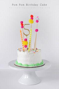 Pastel de cumpleaños con toppers de pompones