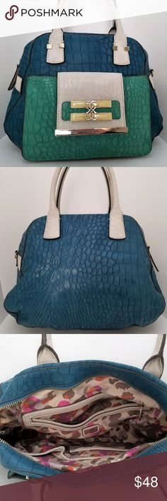 "Guess Teal Crocodile Purse Size:  Width (at base):11""  Height: 8.5""  Depth: 5.5""  Handle Drop: 7""  Product Details:  Type of Material: Guess Teal faux Croco Leather  Color: Teal, Green and Ivory  Lining: Multi Colored Berry Fabric  Pockets: Four Interior Pockets, One Exterior Pocket  Hardware: Polished Silver  Closure: Zipper Top  Add on: Matching Wallet to add for additional price  This Guess Purse is a Smaller handbag made with textured Teal, Green and Ivory Croco faux Leather, detailed by…"