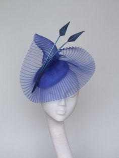 An elegant hand blocked royal blue sinamay fascinator/headpiece with crinoline and feather detail.  An exquisite way to accessorise for that special occasion.   Secured by hat elastic.  Please allow 5 days for this item to be made/  Can also be made in black and red or a combination of both.