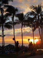 Hula dancers at sunset in torch lighting ceremony and free hula show on Waikiki Beach.