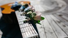 A blurry shot of an acoustic guitar with tiny bouquets of flowers on its neck