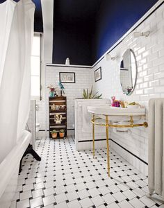 White and blue bathroom with lots of tiles and round mirror
