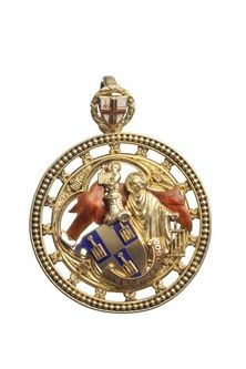 A twentieth-century City of London Girdler's Company livery badge; the badge features the Company's coat of arms, a shield with three gridirons on it, and the motto 'Give Thanks to God'. The design also features Saint Lawrence the Martyr, the patron saint of Girdlers. The shield of the City of London can be seen above. (Museum of London)