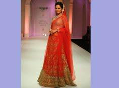 Esha Gupta in a stunning red and gold lehenga from Adarsh Gill's collection 'EVOLUTION' an ode to the contemporary Indian woman'.