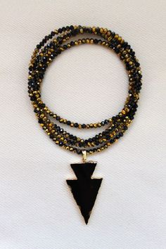 Black and gold beaded necklace with arrowhead pendant