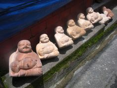 Unpainted buddhas line up along Km 4 Asin Rd.