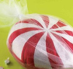 """Christmas Candy Pillow  This """"sweet"""" pillow will be a fun addition to your sofa, bed, armchair or even under the tree. The project uses felt to form the swirls and is wrapped in white tulle."""