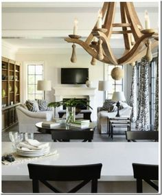 living room arrangement with matching sofas, notable wooden chandelier over dining room table