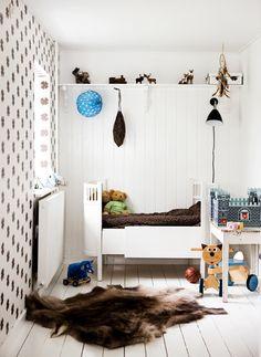simple kids room. fur rug. 1 wallpapered wall.