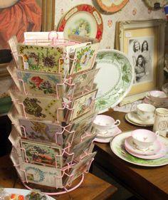 vintage postcards in a pink display rack Store Displays, Collection Displays, Booth Displays, Postcard Display, Rustic Vanity, Lily Bloom, Single Sink, Displaying Collections, Vintage Boutique