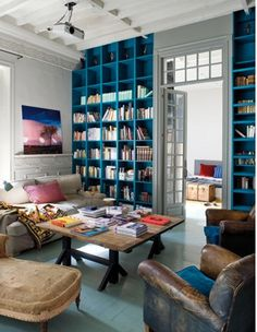 the love for this place is endless: teal painted wood floors, floor to ceiling bookcase, wood beam ceiling, molding, small window paned french doors to bedroom, the couch, the chairs and the pillows!  A total dream place to come home too for sure!
