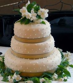 Wedding Cakes: Beige traditional wedding cake with white and green flowers