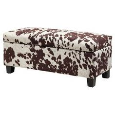 """Bring ranch-chic style to your living room or den seating group with this convenient storage bench, featuring cowhide-inspired upholstery and ample space for throws and board games.  Product: BenchConstruction Material: Cotton, wood and foamColor: Cream, white and brownFeatures: Lift-top storageDimensions: 18"""" H x 43"""" W x 17"""" DCleaning and Care: Professional cleaning recommended"""