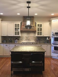 Updated kitchen with a wood hood and glass tile
